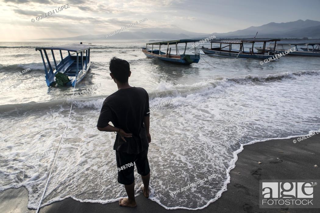 Stock Photo: A local men checks his wooden boats during bad weather in Gili Air, Gili Islands, Indonesia.