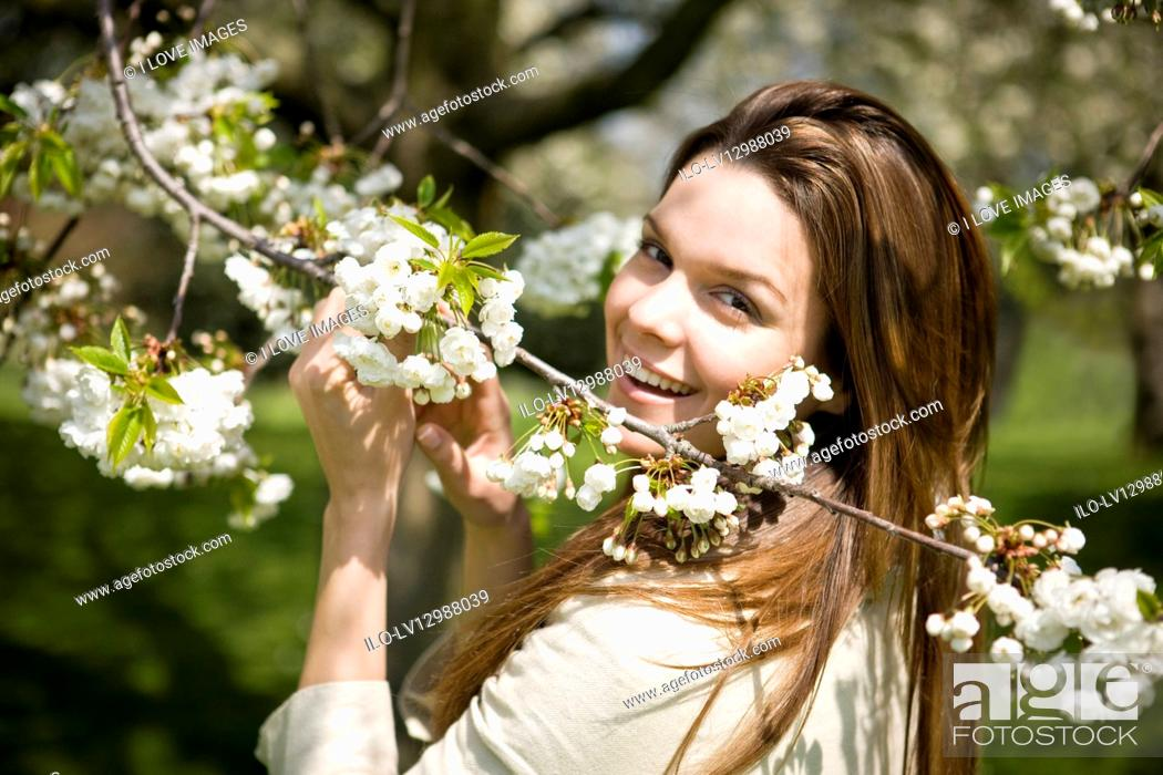 Stock Photo: A young woman holding a branch of spring blossom.