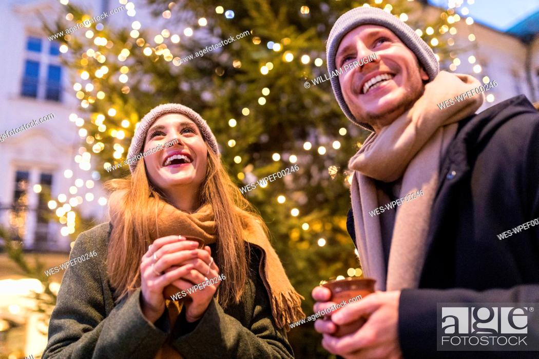 Stock Photo: Laughing young couple drinking mulled wine at Christmas market.