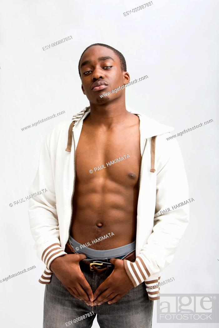 Stock Photo: Young dark skinned handsome guy standing like a macho with both hands on his belt, wearing an open white hooded shirt with his hood on and showing his six pack.