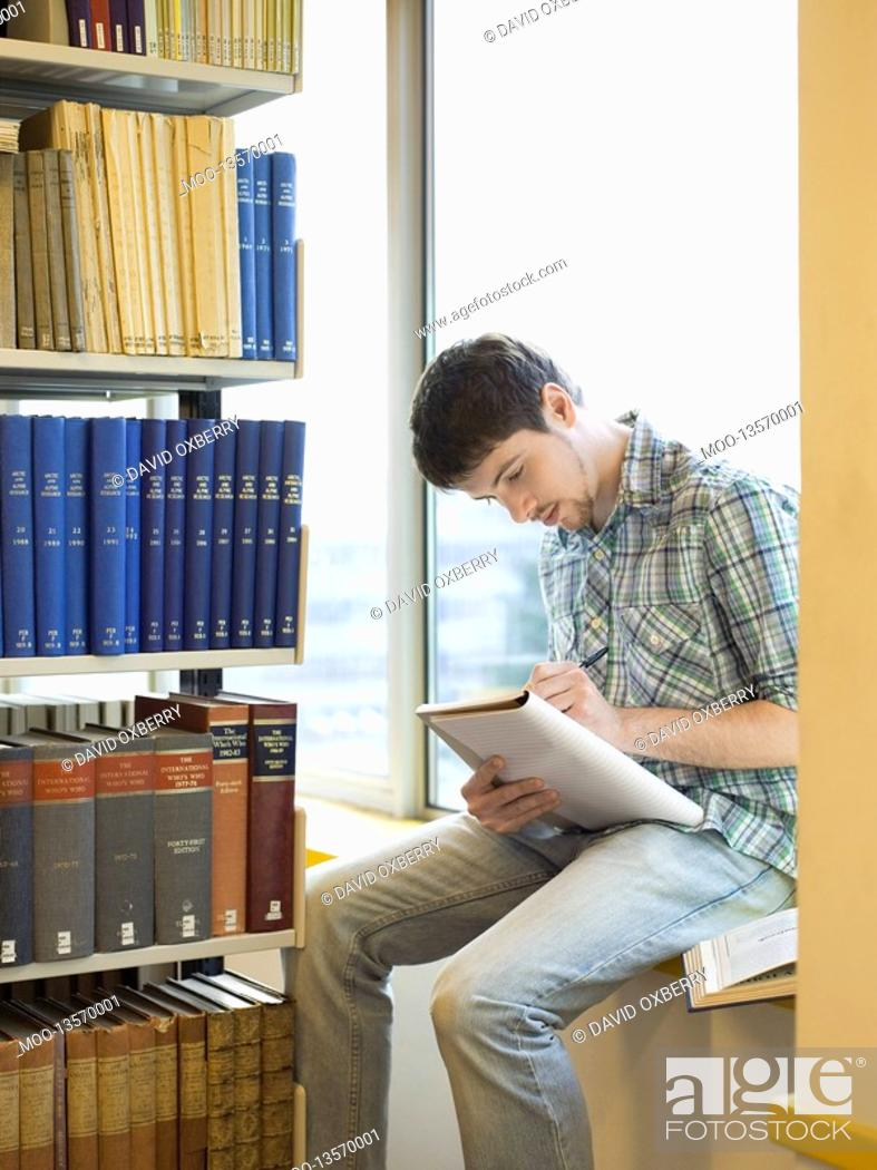 Stock Photo: Student sitting on windowsill in library taking notes.