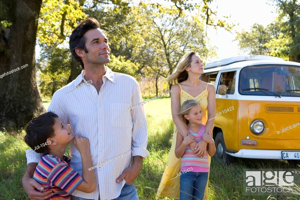 Stock Photo: Parents embracing son and daughter 5-9 in field by camper van, low angle view.