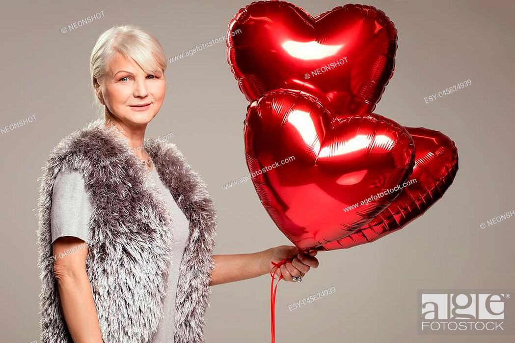 Stock Photo: Elegant adult woman holding red balloons, valentine's day.