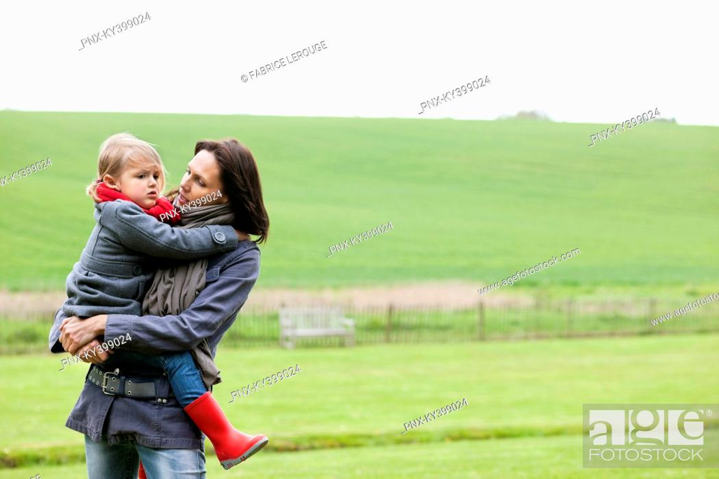 Stock Photo: Woman carrying her daughter in a field.