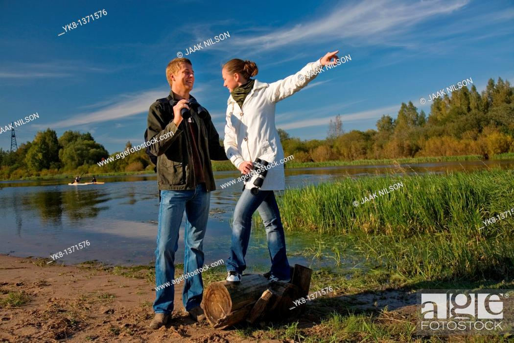 Stock Photo: Young couple birdwatching with binoculars by river water pointing away.