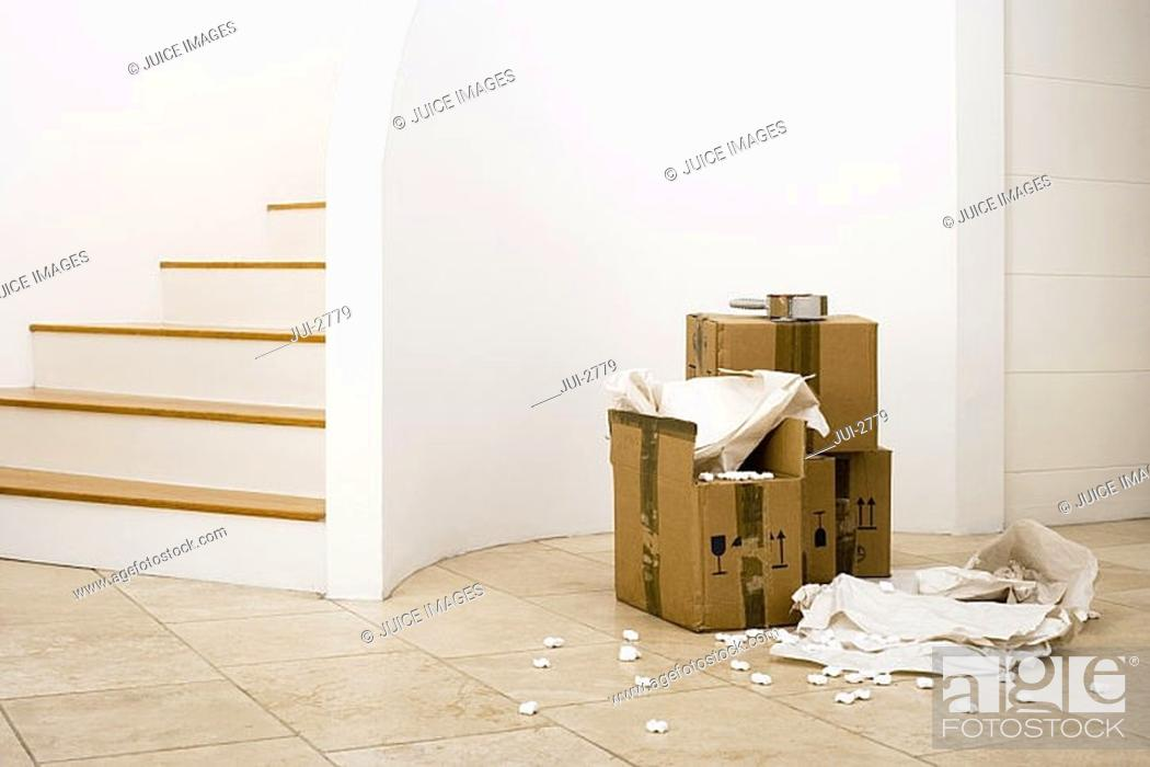 Stock Photo: Small stack of boxes, paper and packing foam beside staircase in sparse room.