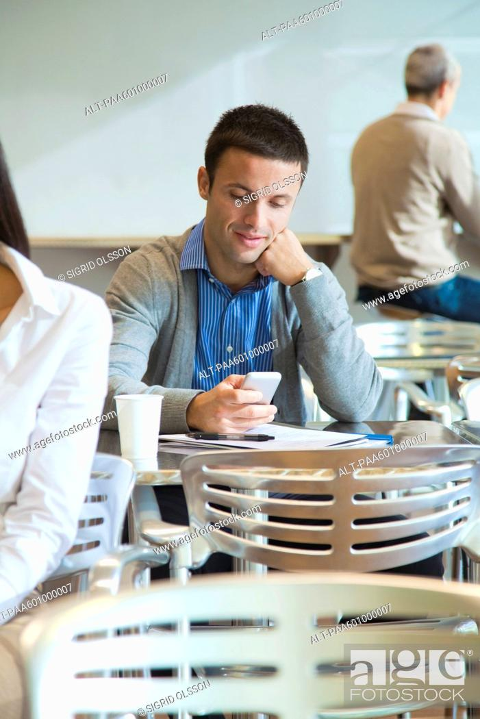 Stock Photo: Man using cell phone in cafeteria.