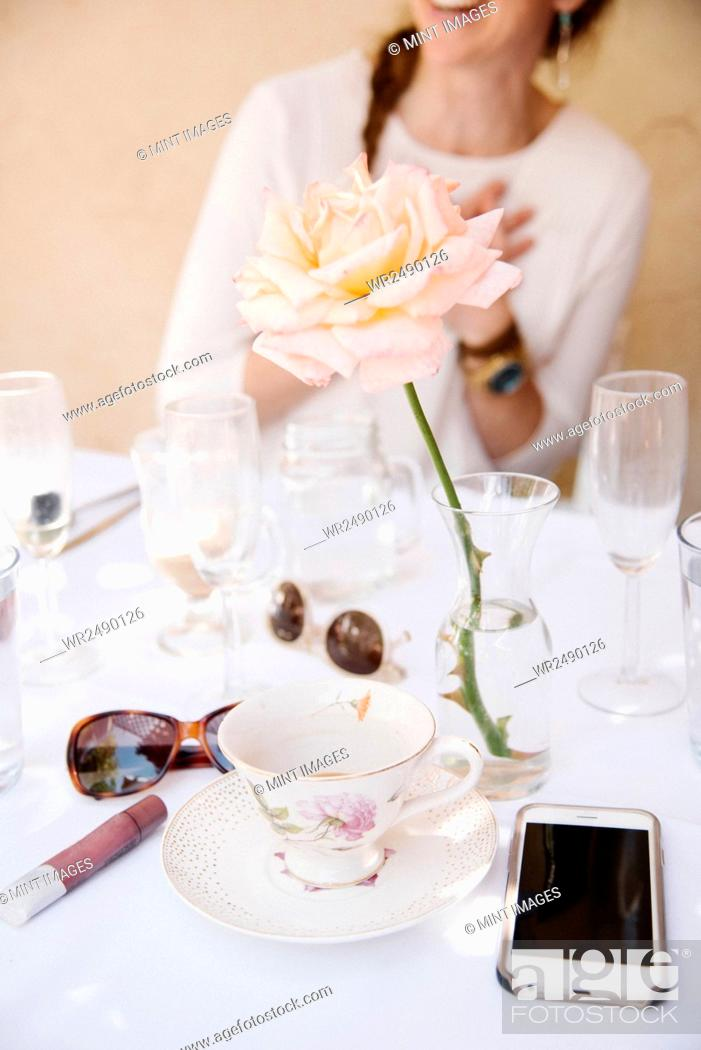 Imagen: Close up of a rose in a vase on a table with cups and glasses, a cell phone and sunglasses.