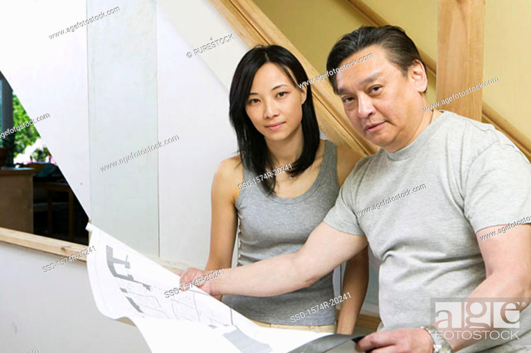 Stock Photo: Portrait of a mid adult man holding a blueprint with a young woman beside him.