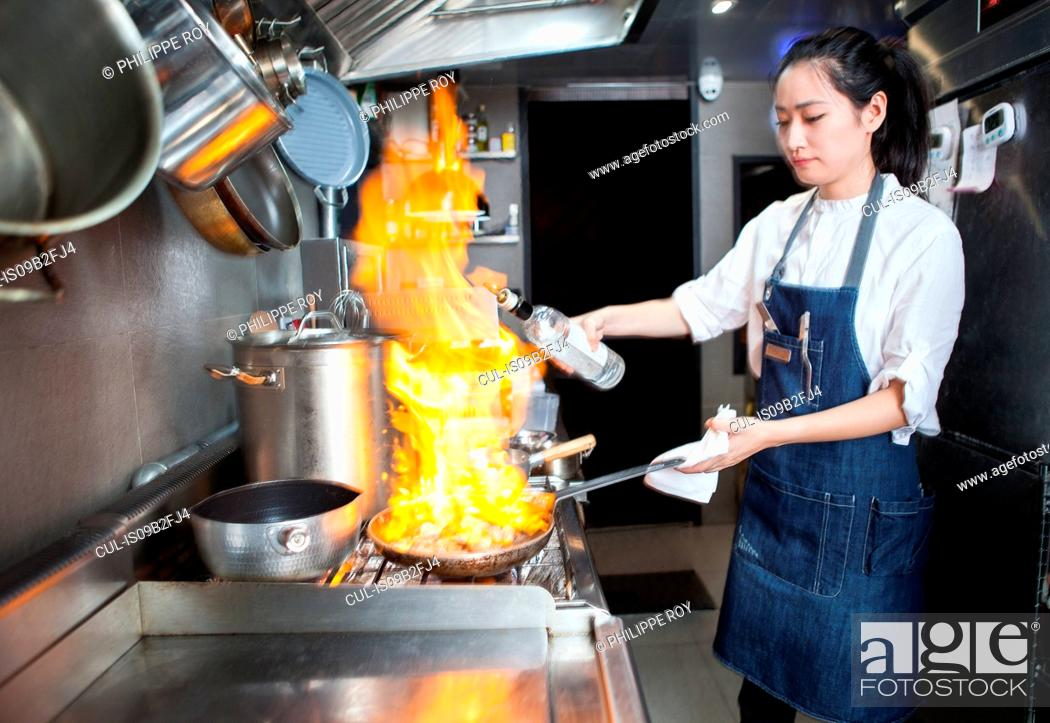 Stock Photo: Chef flambeing in commercial kitchen.