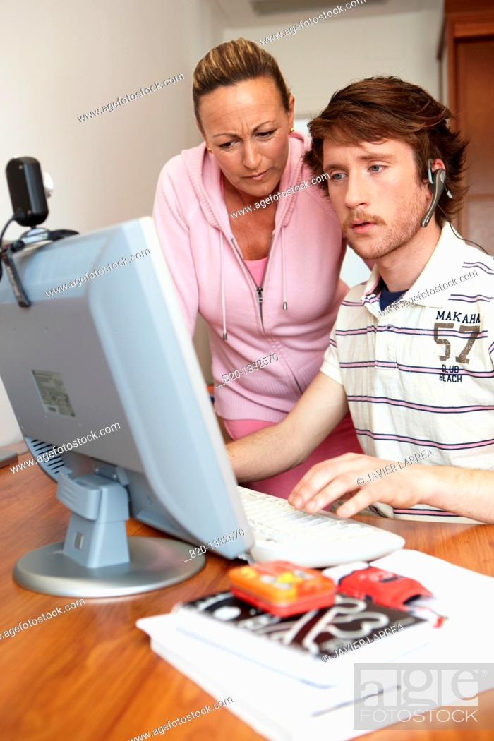 Stock Photo: Mother and son looking at PC in room.