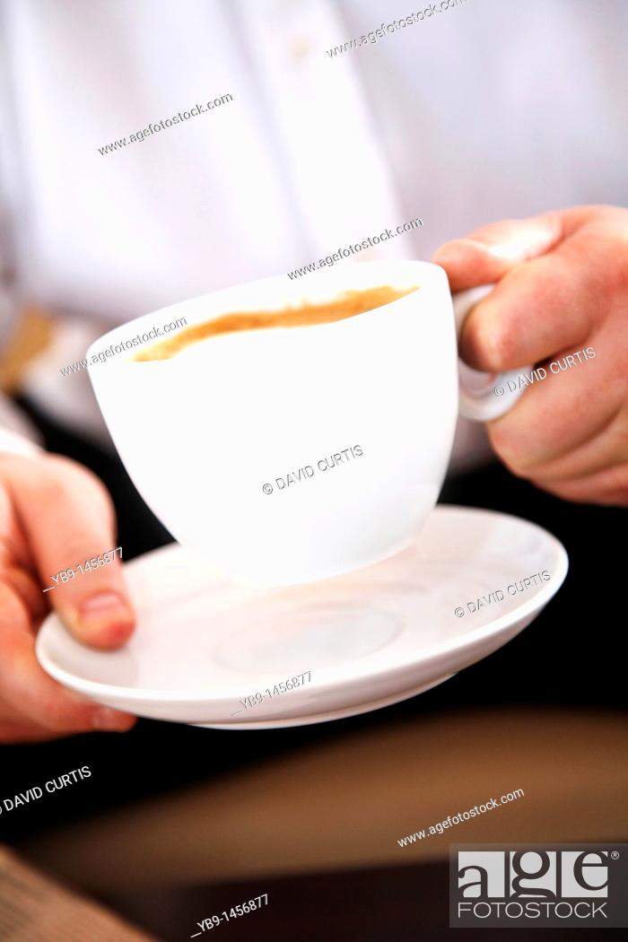 Stock Photo: Man holding a cup of Cappuccino.