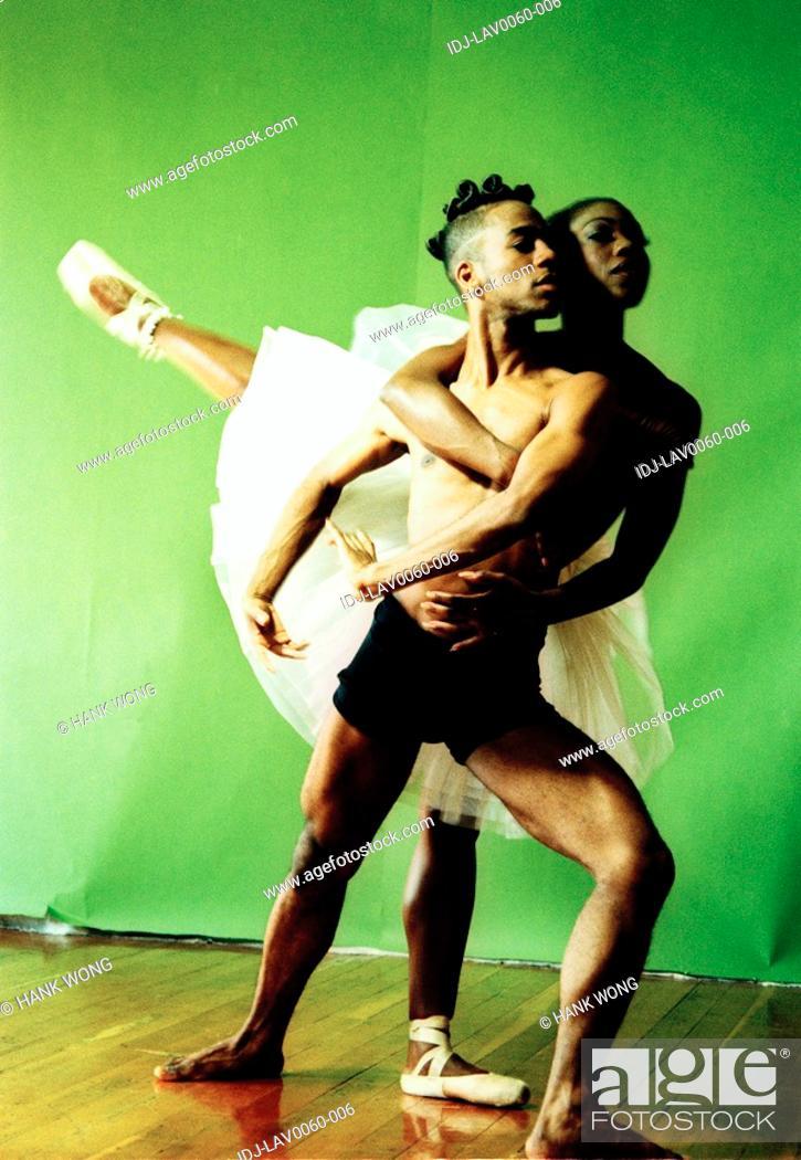 Stock Photo: Female ballet dancer hugging a male ballet dance from back and raising her leg.