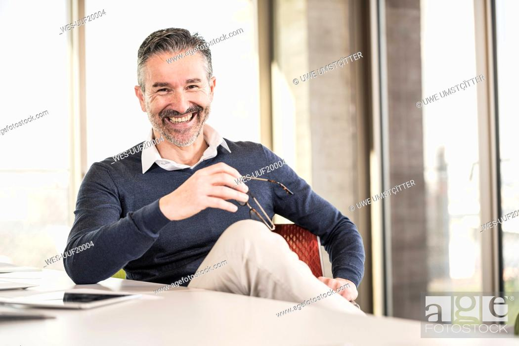 Stock Photo: Portrait of a happy mature businessman sitting at desk in office.
