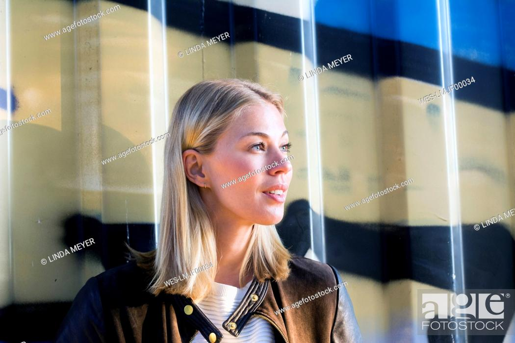 Stock Photo: Portrait of blond woman in front of container looking at distance.