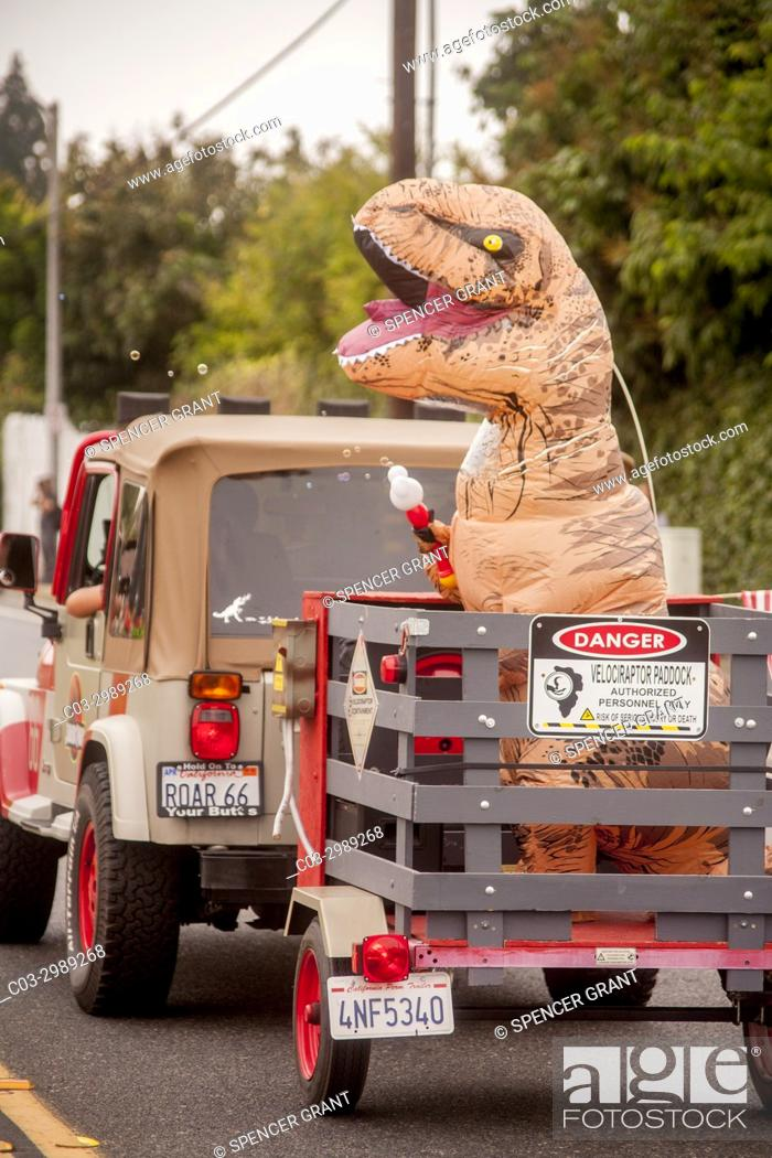 """Stock Photo: A costumed Jurassic monster gets a ride in a trailer behind a Jeep in a city anniversary parade in Fountain Valley, CA. Note """"""""Roar 66"""""""" license plate."""