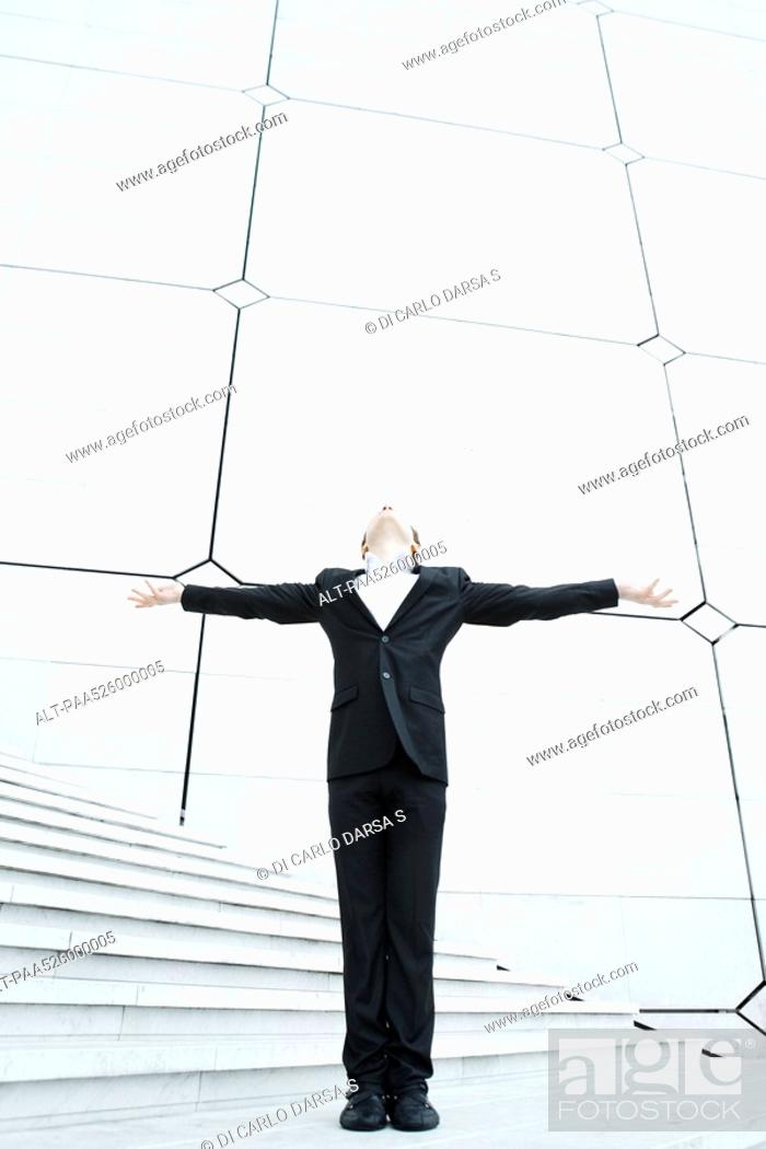 Stock Photo: Business woman standing at foot of stairs with arms outstretched leaning back and looking up.