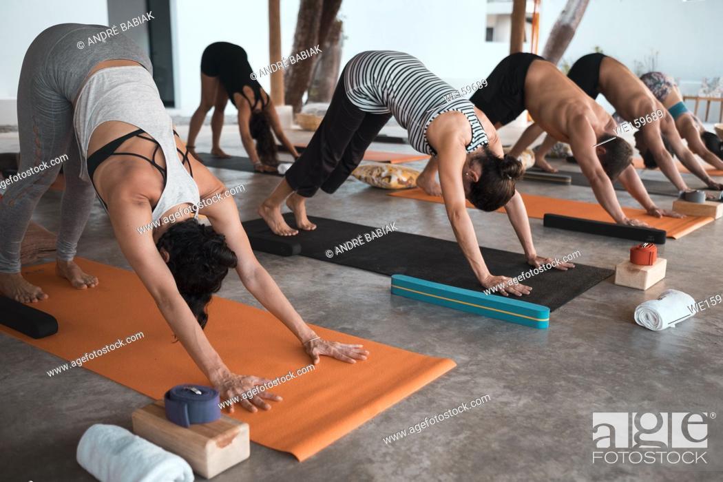 Stock Photo: Multiple people exercising yoga on mats.