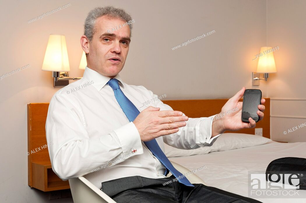 Stock Photo: Business man sitting in hotel room in animated conversation.