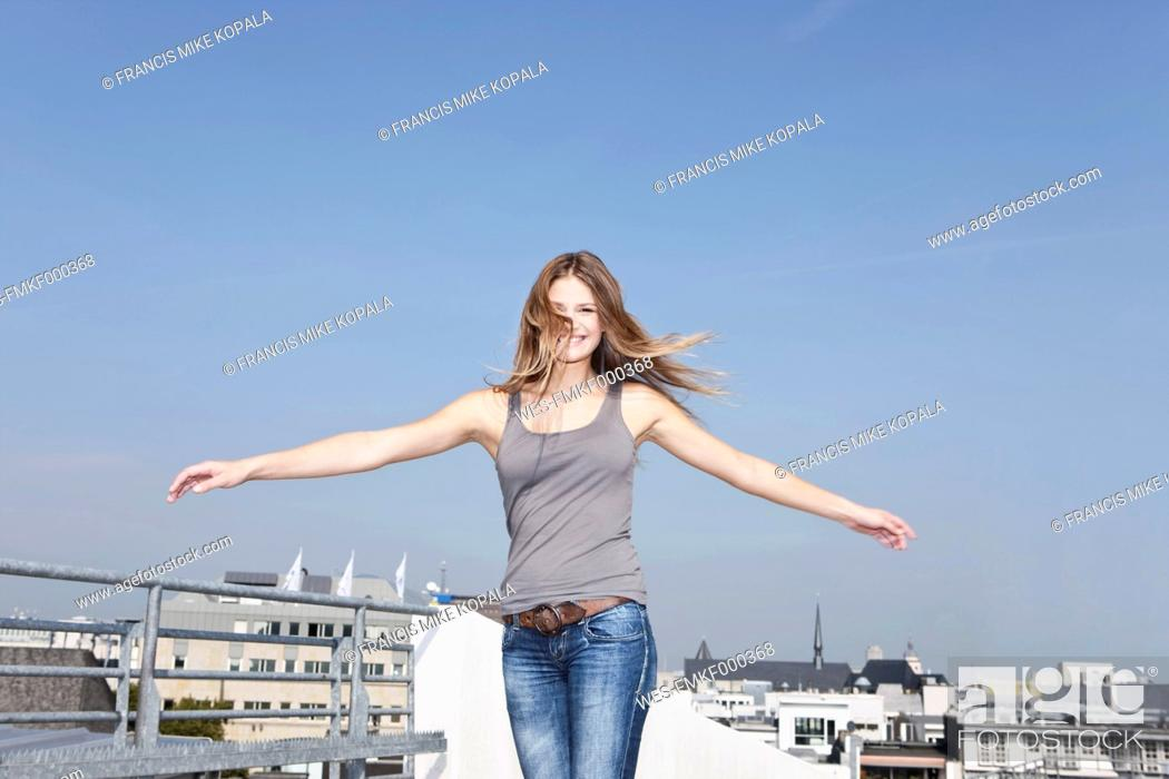 Stock Photo: Germany, Cologne, Young woman at parking building, smiling, portrait.