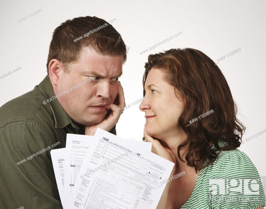 Stock Photo: Married couple with United States 1040 tax forms feeling anxious about their taxes.
