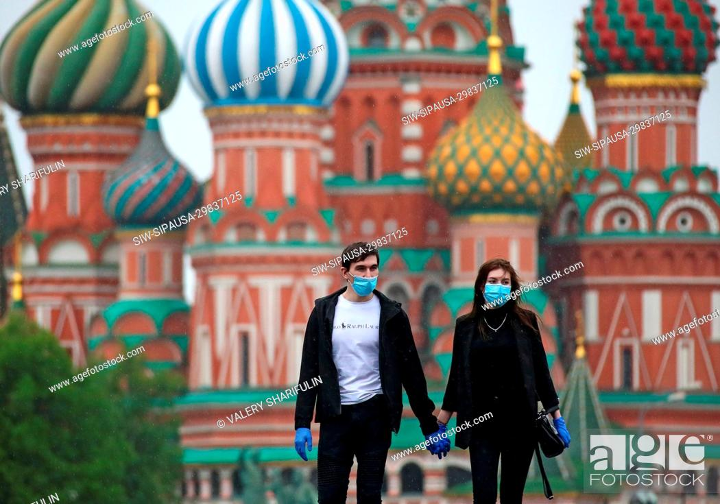 Stock Photo: MOSCOW, RUSSIA - MAY 12, 2020: Young people hold hands as they walk in central Moscow. Moscow Mayor Sergei Sobyanin made mandatory wearing face masks and gloves.