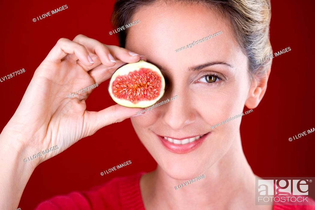 Stock Photo: A mid adult woman holding half a fig in front of her eye.