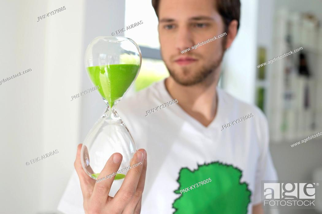 Stock Photo: Man looking at an hourglass with green sand in it.