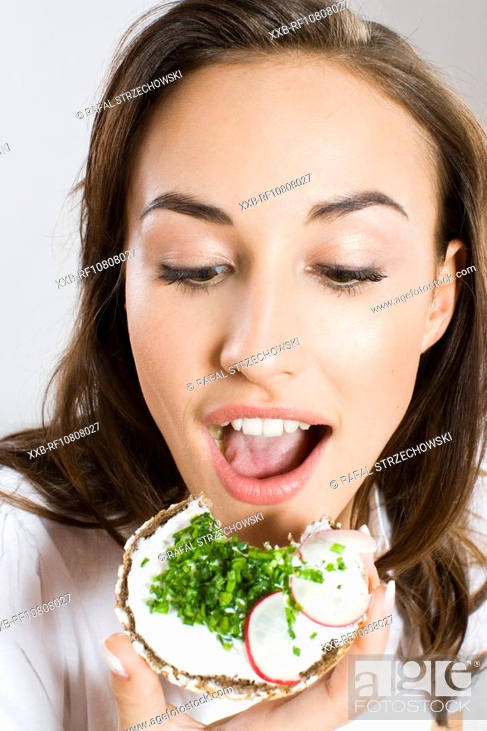 Stock Photo: Young woman eating sandwich.