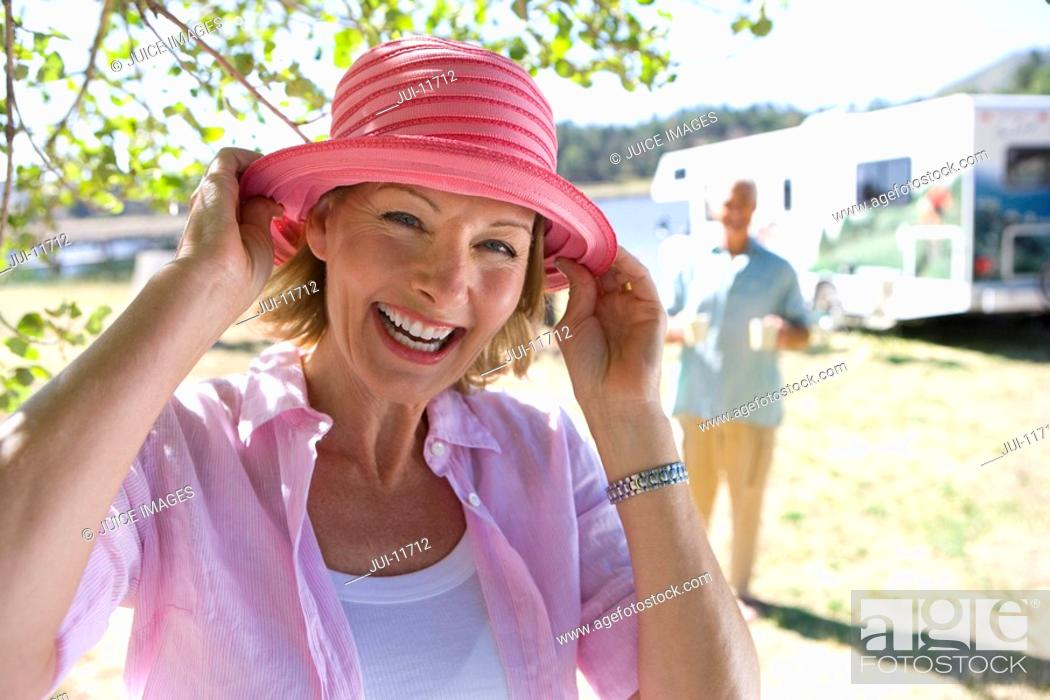 Stock Photo: Mature woman with hat by husband and motor home outdoors, smiling, portrait, close-up.