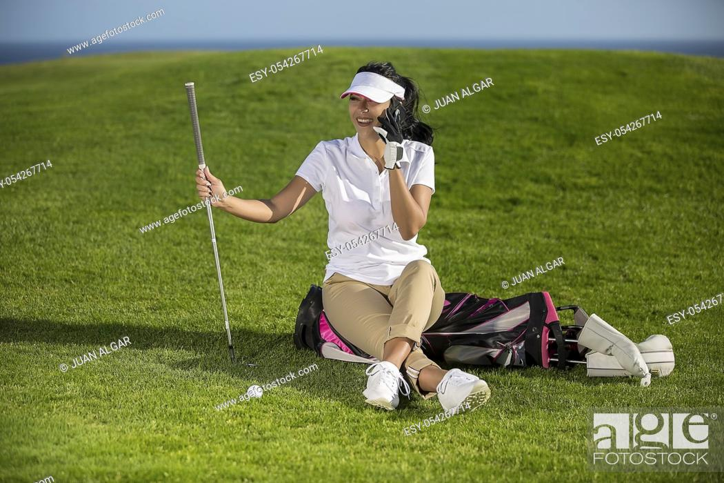 Stock Photo: Cheerful stylish woman relaxing on golf course sitting on bag and speaking on phone happily.