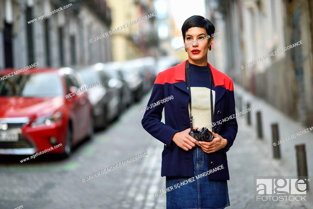 Photo de stock: Portrait of fashionable young woman with camera on the street.