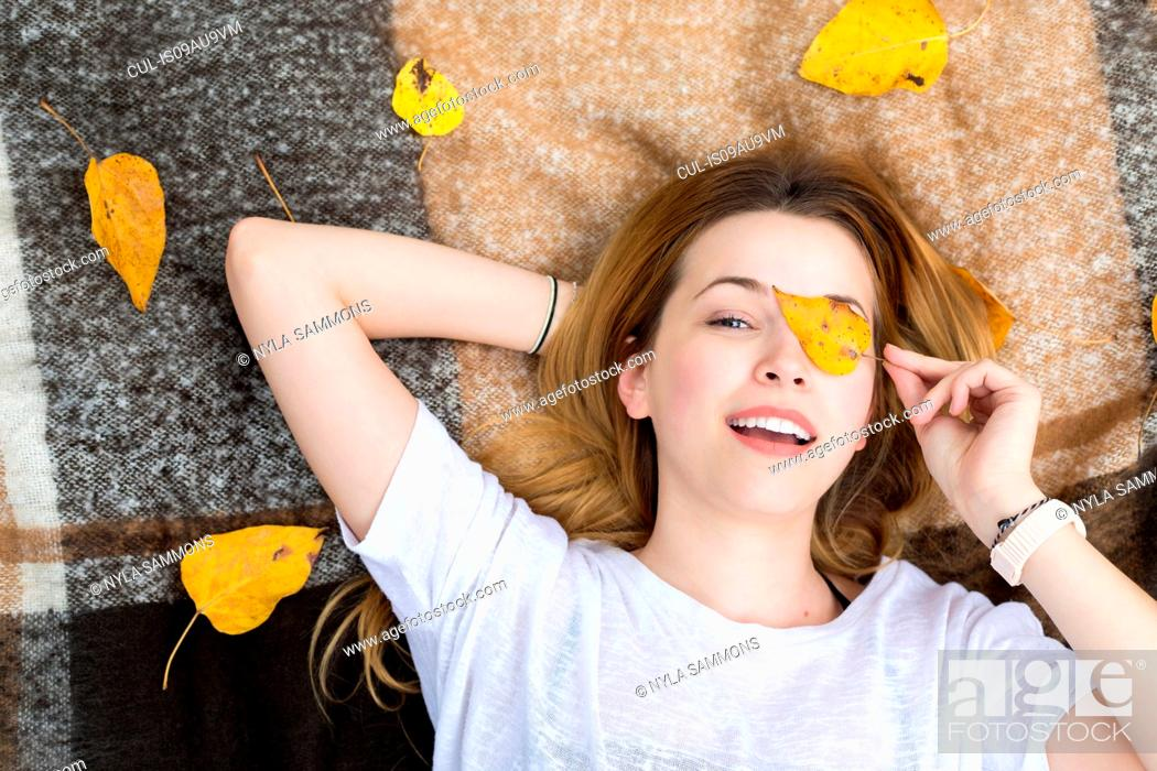 Stock Photo: Young woman lying on blanket, covering eye with leaf.