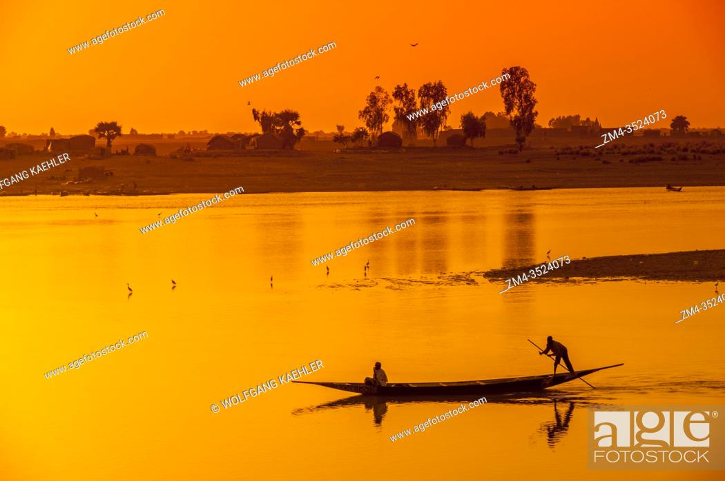 Stock Photo: Local people in wooden canoes at sunset on the Bani River in Mopti in Mali, West Africa.