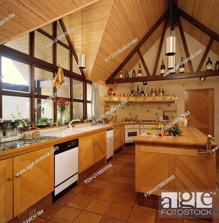 Wooden apex ceiling in modern pale wood kitchen with ...