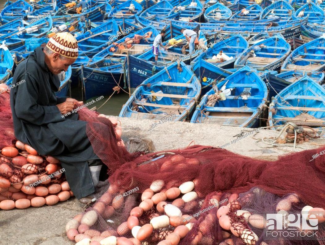 Stock Photo: Man repairing fishing nets, blue boats in the fishing harbour of Essaouira behind, Essaouira, Morocco.