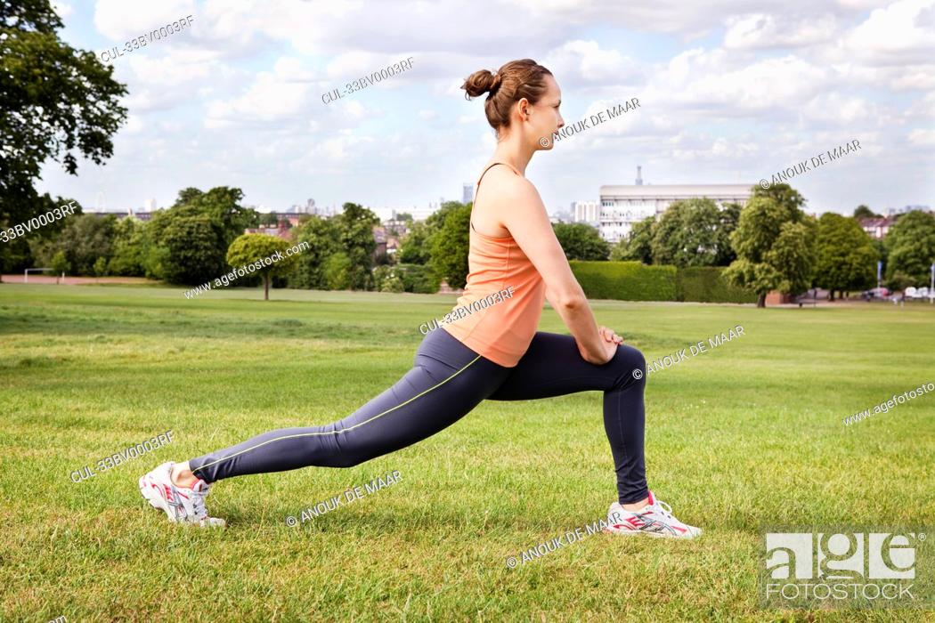 Stock Photo: Woman stretching in park.