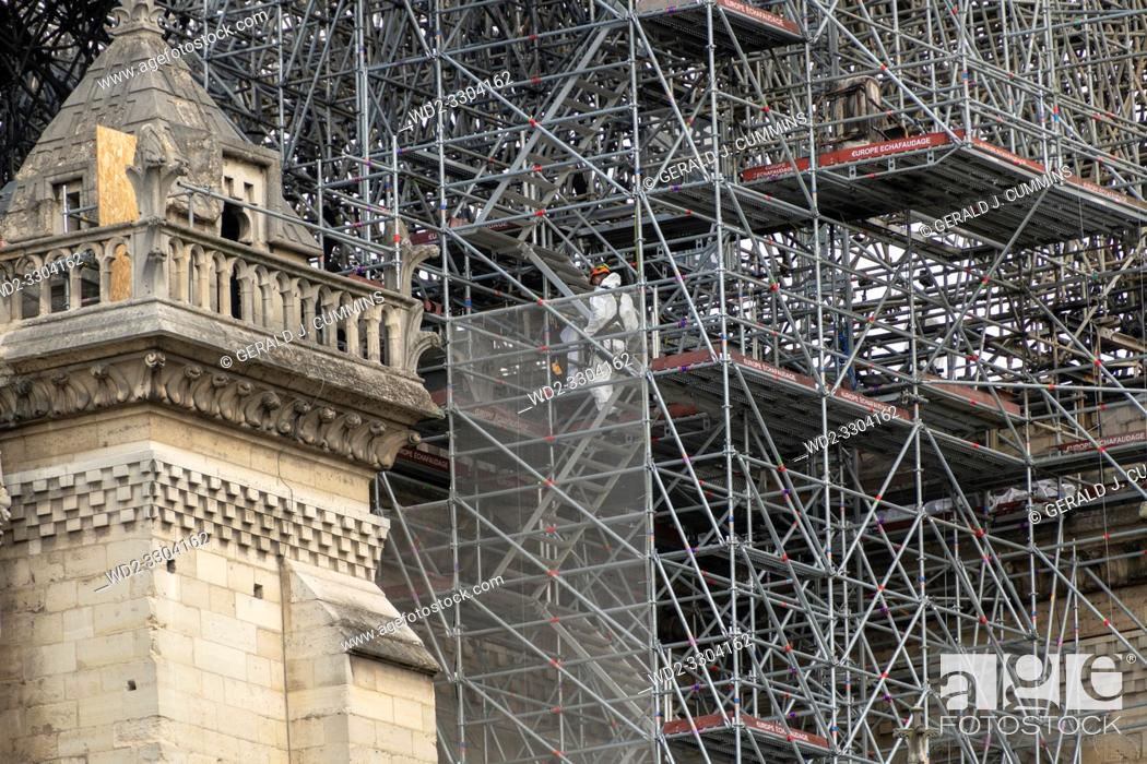 Stock Photo: PARIS, FRANCE - 19 APRIL 2019 Notre Dame cathedral, a man positions sandbags along the edge of the walls. The remains of the melted scaffolding behind him is.