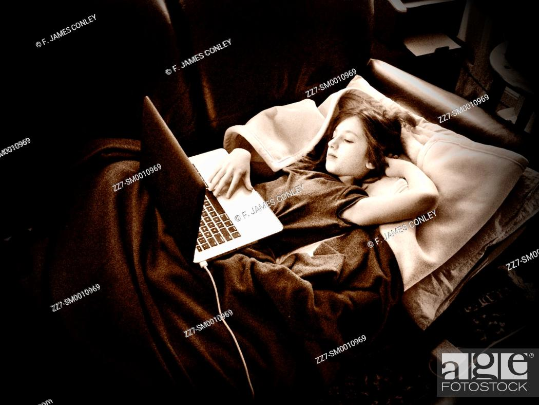 Imagen: A young girl works on a laptop computer.