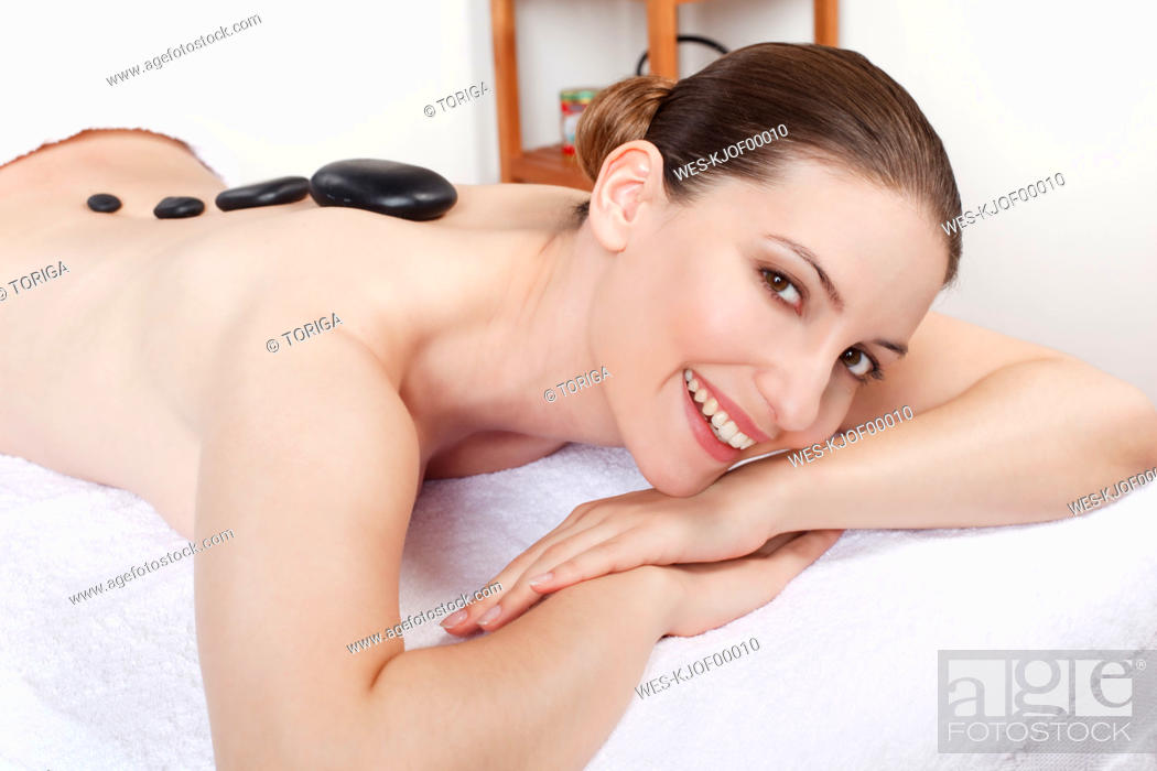 Stock Photo: Woman having a hot stone treatment, smiling, portrait.