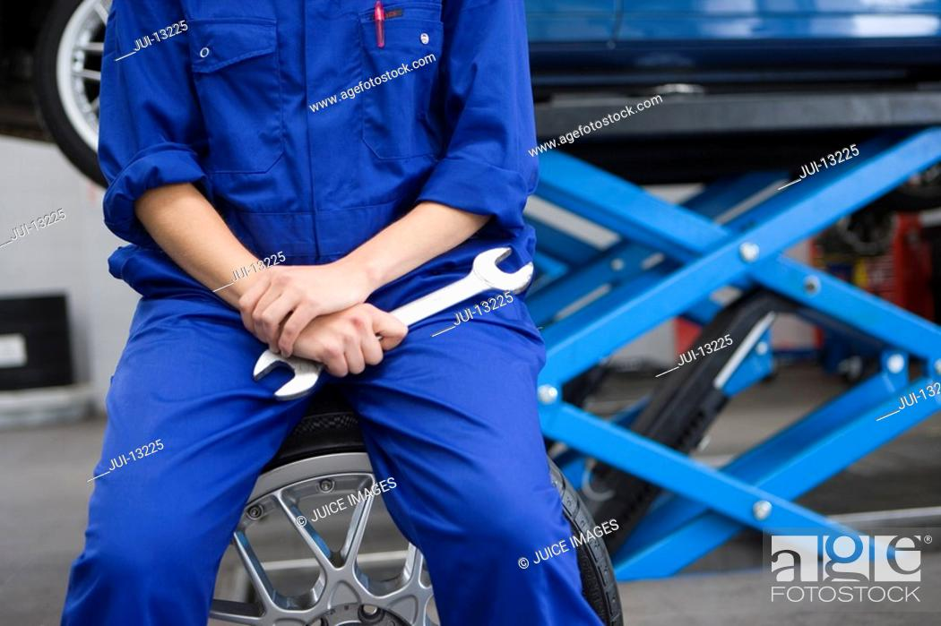 Stock Photo: Female mechanic with wrench by elevated car, mid section.