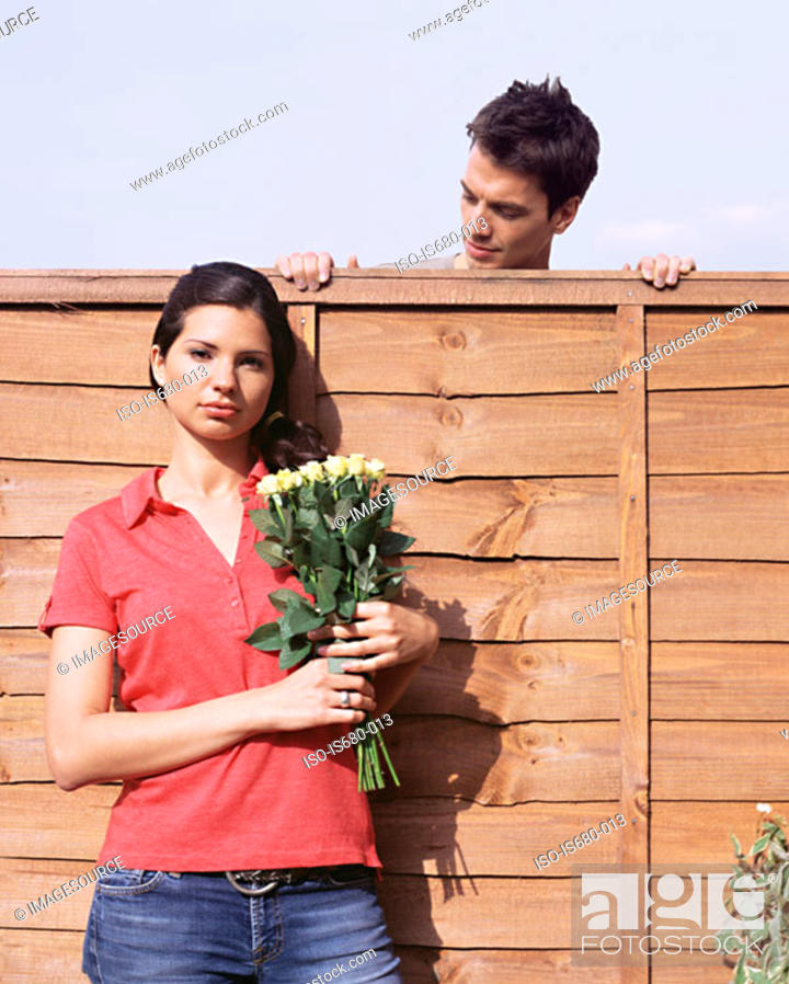 Stock Photo: Man looking at woman over garden fence.