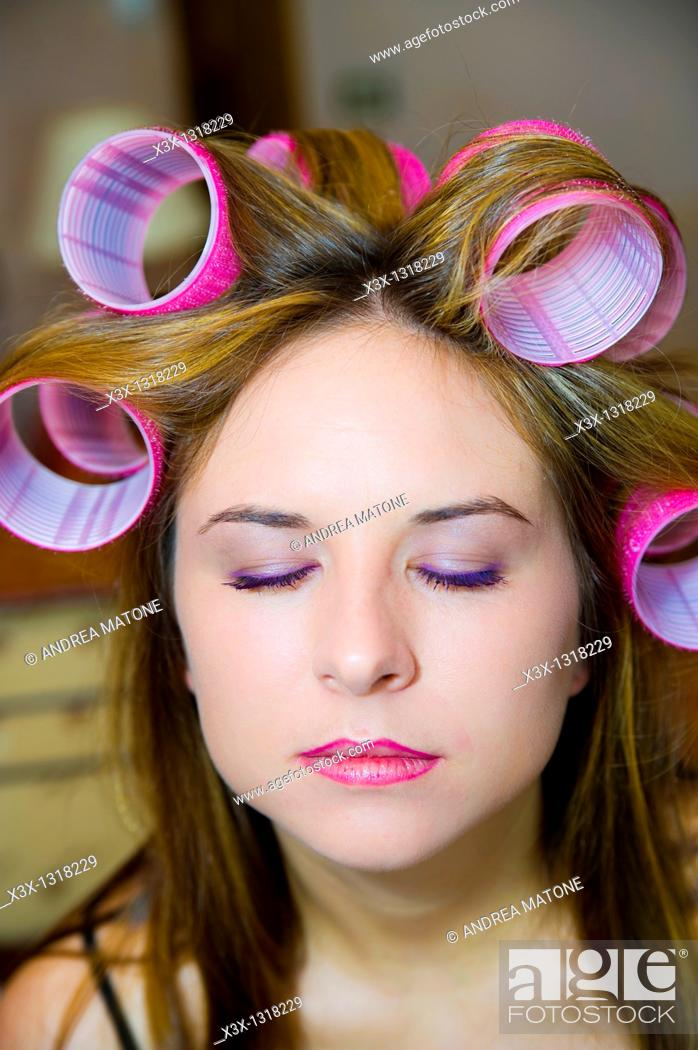 Stock Photo: Woman's hair on curlers with eyes closed.