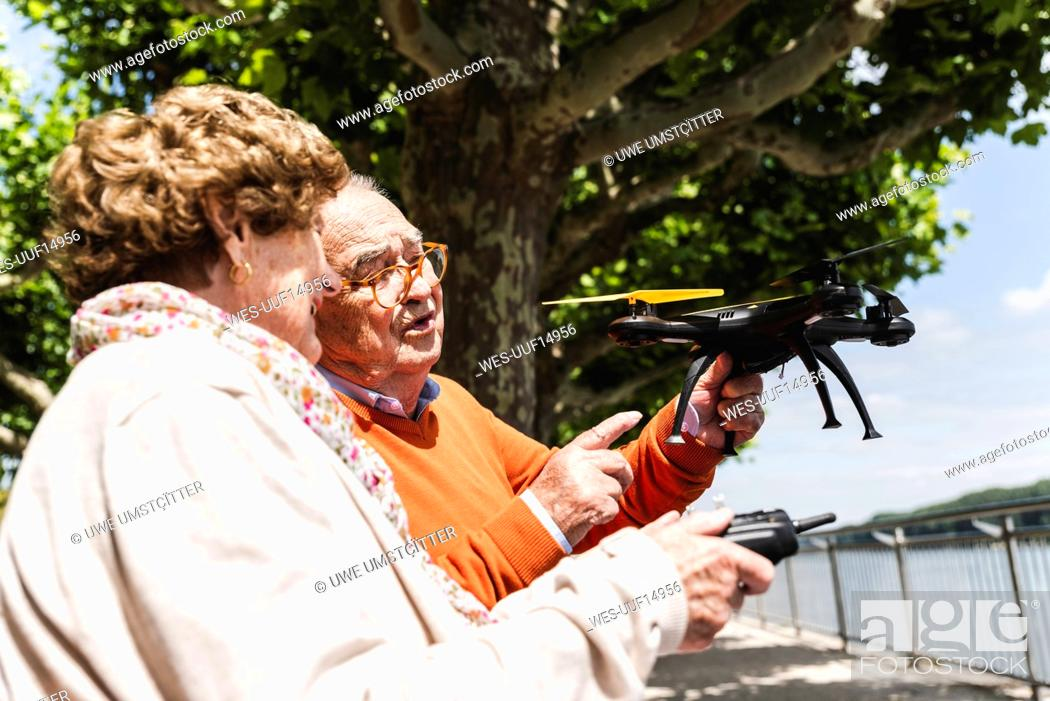 Stock Photo: Senior couple playing with a drone in park.