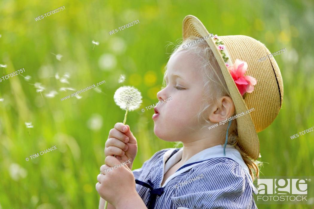 Stock Photo: Germany, Bavaria, Girl blowing dandelion seed.