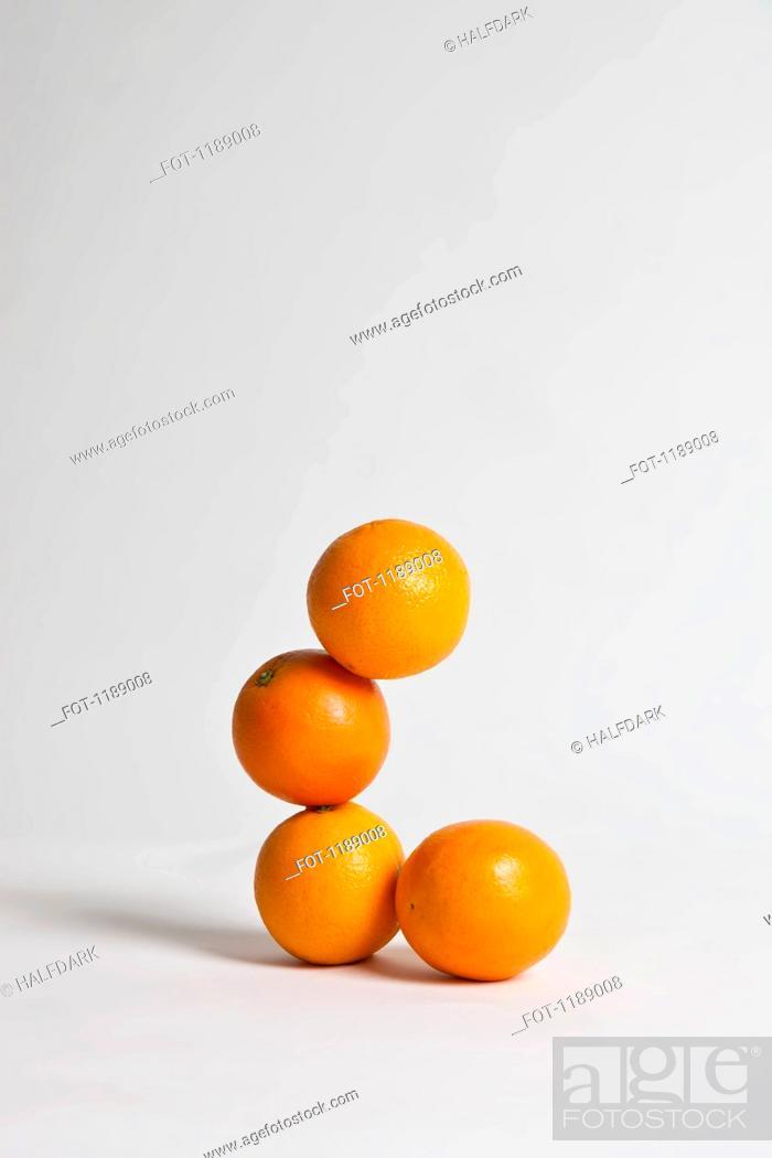 Stock Photo: Oranges stacked precariously, studio shot.