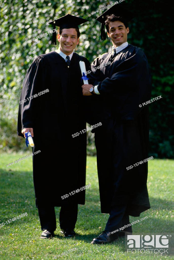 Stock Photo: Portrait of two young men wearing graduation outfits holding diplomas.
