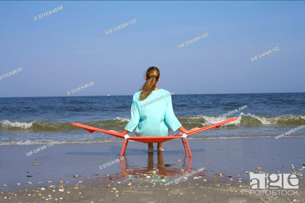 Stock Photo: Woman sitting on a beach chair while looking at the sea.