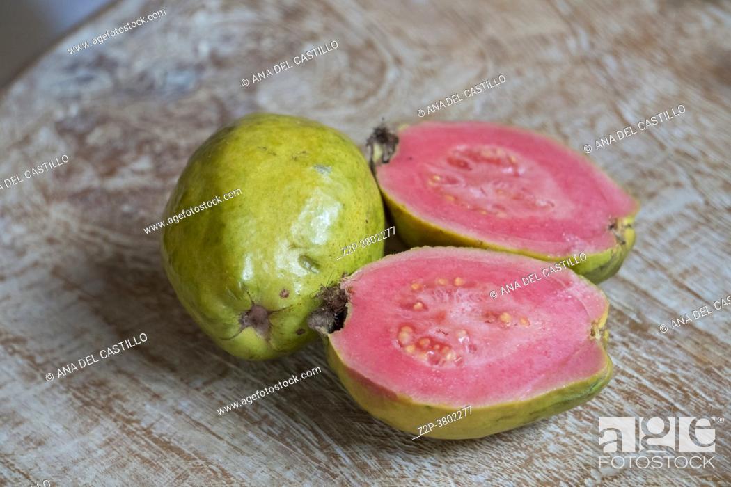 Stock Photo: Fresh pink goiaba on wooden table.
