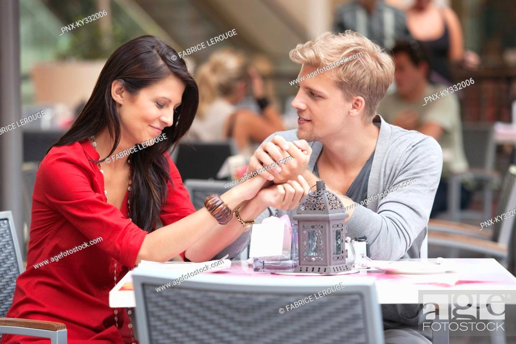 Stock Photo: Young man holding hands of his girlfriend in a restaurant.